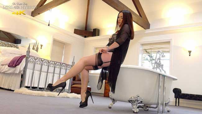 Sexy seamed stockings, long legs and sky high heels Miss Hybrid masturbating on the bed.