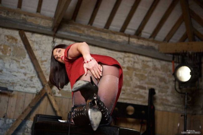 Miss Hybrid thigh high leather boots and sex toys playing in the dungeon.